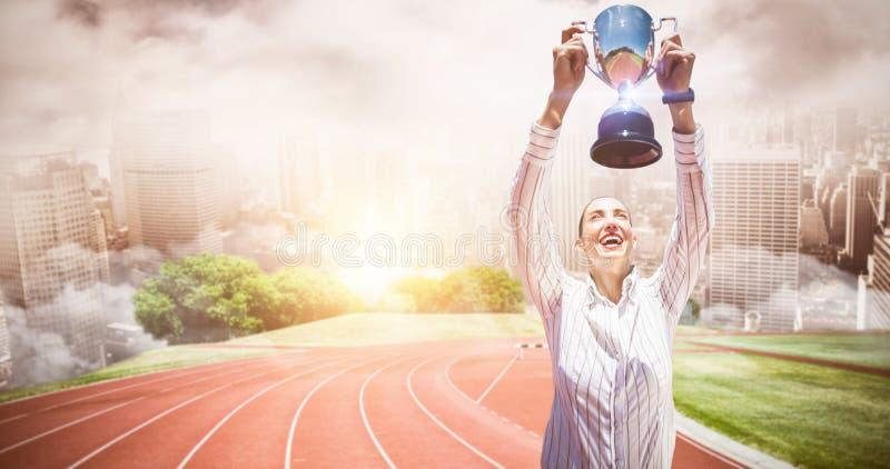 Составное изображение успешной коммерсантки поднимая трофей стоковые фотографии rf