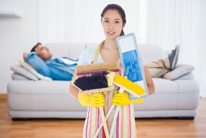 Составное изображение хмуриться удерживание женщины чистит щеткой и mops стоковые изображения rf