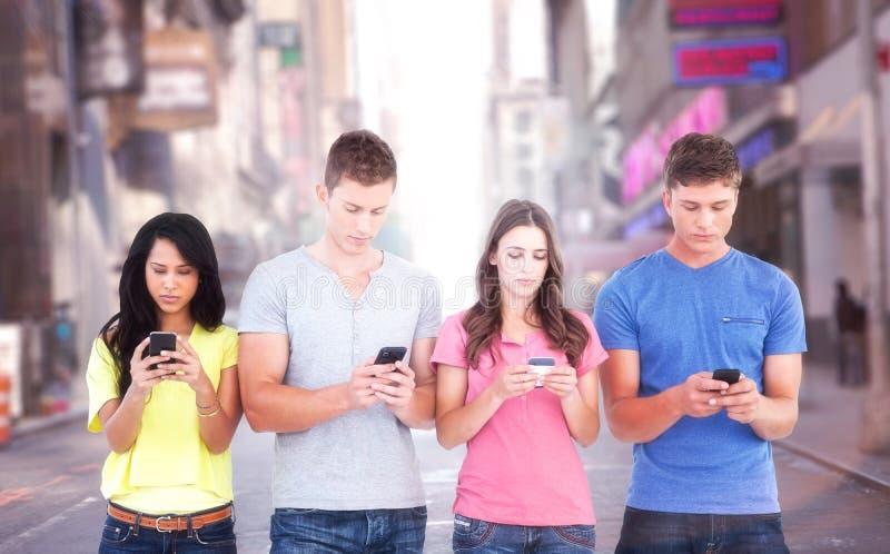 Составное изображение 4 людей стоя около одина другого и отправляя СМС на их телефонах стоковое изображение rf
