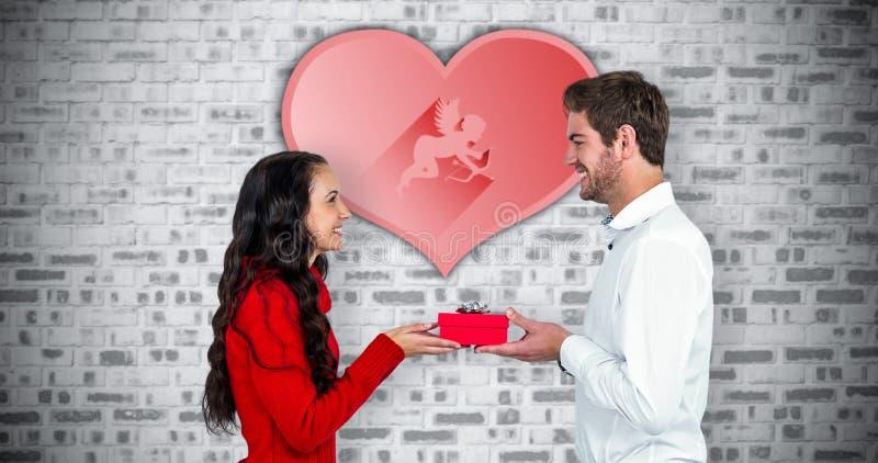 Составное изображение excited молодых пар держа подарочную коробку стоковое изображение