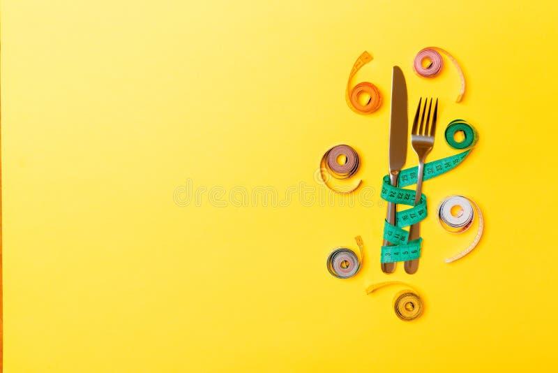Состав взгляда сверху вилки и нож с покрашенный balled измеряя ленты на желтой предпосылке с пустым космосом для ваших идей стоковое изображение rf