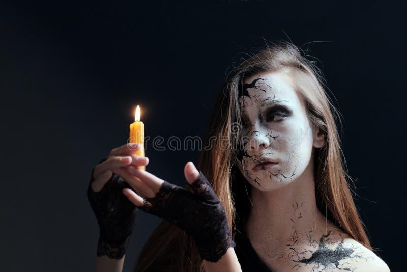 Состав в стиле хеллоуина Маленькая девочка с длинными волосами при отказы покрашенные на ее стороне держит горящую свечу Темный б стоковые изображения rf