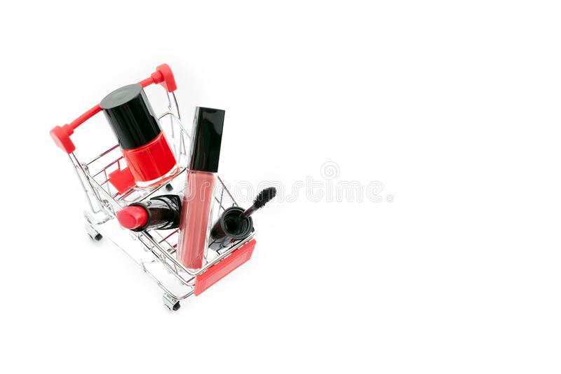 Состав в pushcart изолированном на белой предпосылке Красная губная помада, тушь, розовый лоск губы, порошок, маникюр состав стоковое изображение