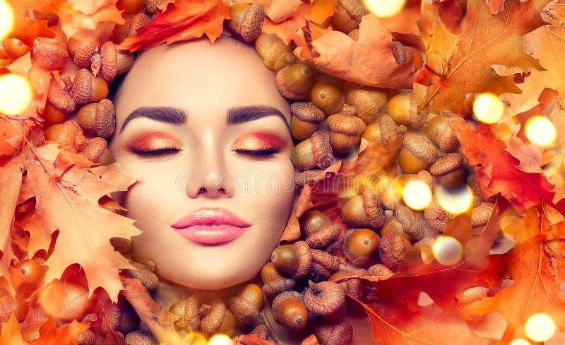 Состав женщины осени Красивый портрет стороны девушки модели осени с яркими желтыми, красными и оранжевыми листьями цвета стоковая фотография