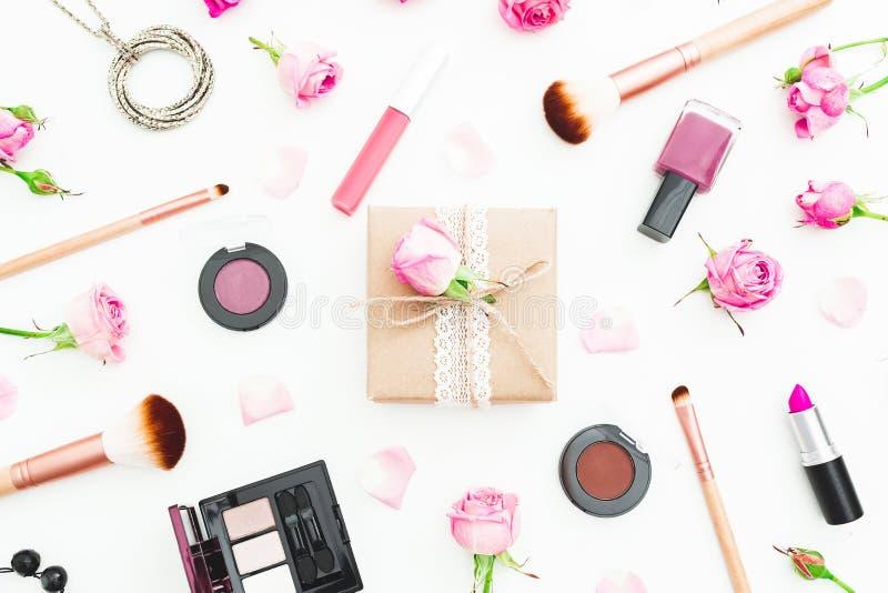 Состав женщины с подарочной коробкой, цветками роз, косметиками и щетками на белой предпосылке Взгляд сверху Плоское положение стоковые фотографии rf