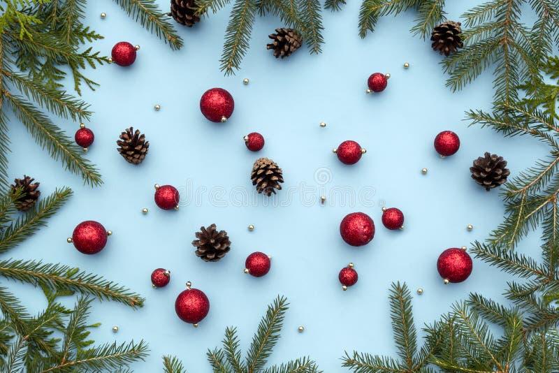 Состав зимы рождества или Нового Года Красные игрушки, елевые ветви ели, конусы сосны, декоративные орнаменты рождества на сини стоковое фото rf