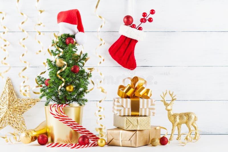 Состав зимы с подарком рождества или присутствующими коробками, елью и золотыми украшениями праздника на деревянной предпосылке стоковые фотографии rf