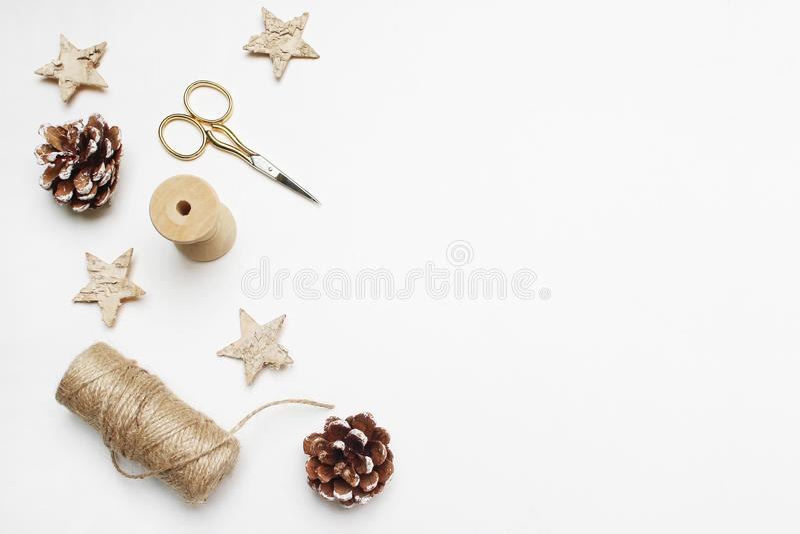 Состав изображения запаса рождества праздничный введенный в моду Pinecones, золотые ножницы, веревочка и деревянные звезды на бел стоковые изображения