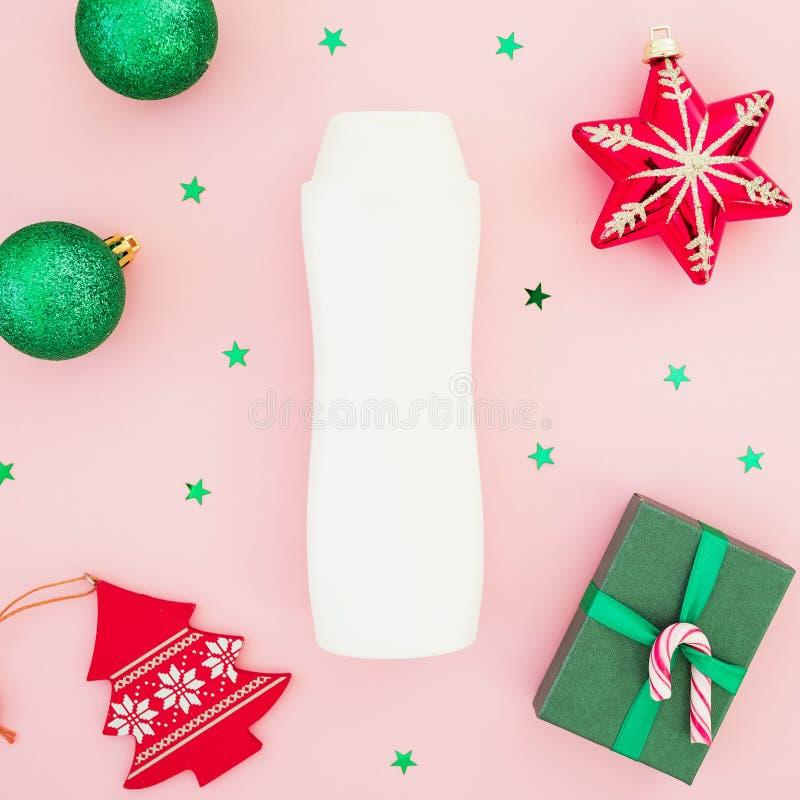 Состав красоты рождества Подарочная коробка рождества, шампунь, игрушки и блестящий confetti на розовой предпосылке Плоское полож стоковое фото rf