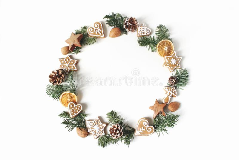 Состав круга рождества флористический Венок ветвей ели, конусов сосны, печений пряника и сухих оранжевых кусков стоковые изображения rf