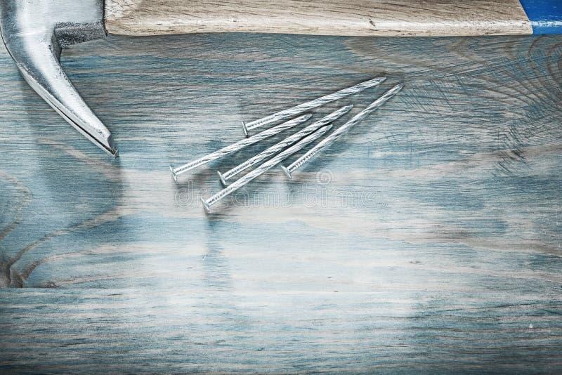 Состав ногтей молотка с раздвоенным хвостом на конструкции co деревянной доски стоковое фото