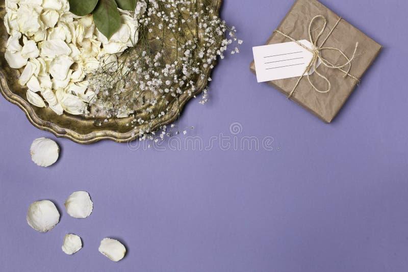 Состав осени с сухими лепестками белых роз и гипсофилы на красивом винтажном подносе, подарке в оболочке в бумаге ремесла на a стоковые фото