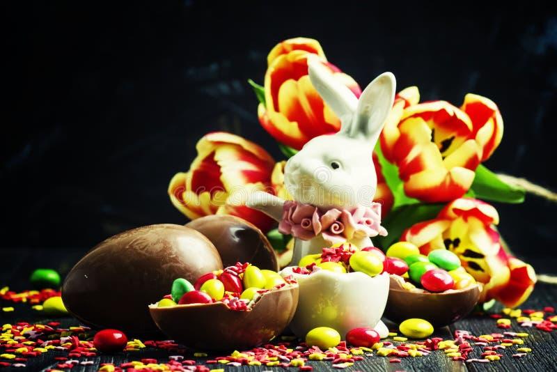 Состав пасхи: кролик, яичка шоколада и помадки, красный тюльпан стоковые изображения