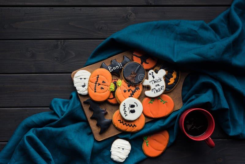состав печений хеллоуина на деревянной доске и голубой ткани с чашкой стоковая фотография
