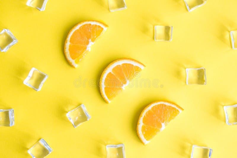 Состав предпосылки взгляда сверху тропический сделал из оранжевых кусков плода и кубов льда абстрактных на желтом цвете стоковая фотография