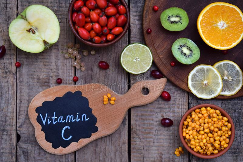 Состав продуктов содержа аскорбиновую кислоту, витамин C - цитрус, киви, крушина моря, яблоко, собака поднял Взгляд сверху Плоско стоковые изображения rf