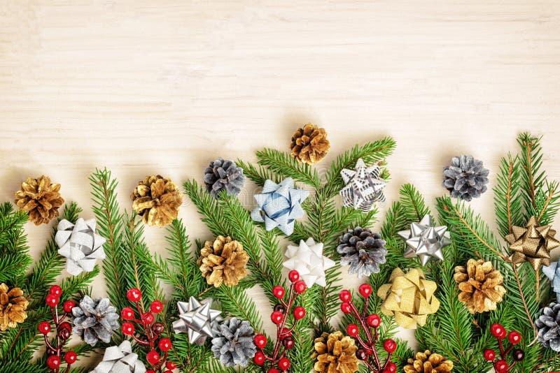 Состав рождества ветвей ели украшенных с красными ягодами, золотыми и серебряными конусами и смычками Пустой космос для текста стоковое фото
