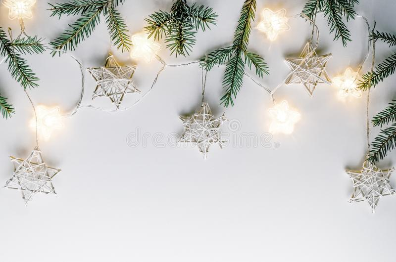 Состав рождества в стиле Eco Ветви ели, handmade звезды и электрические лампочки на белой предпосылке стоковые изображения