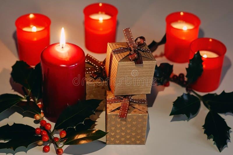 Состав рождества и Нового Года Свечи, подарочные коробки и ветвь Lit падуба стоковое фото
