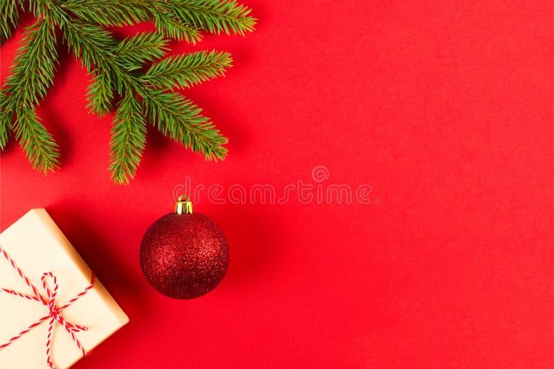 Состав рождества на красной предпосылке Зеленые ветви ели, коробка Xmas присутствующие и украшение стоковое фото