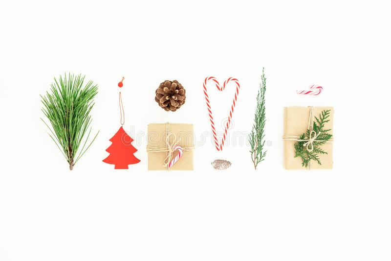 Состав рождества сделал из подарков с тросточкой конфеты, ветвью сосны и конусом сосны на белой предпосылке Новый Год принципиаль стоковое изображение