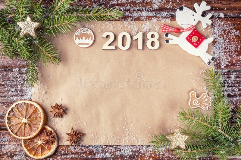 Состав рождества с датой года 2018 на винтажной бумаге в поднимающем вверх рамки Елевые ветви, положение плоское стоковое фото rf