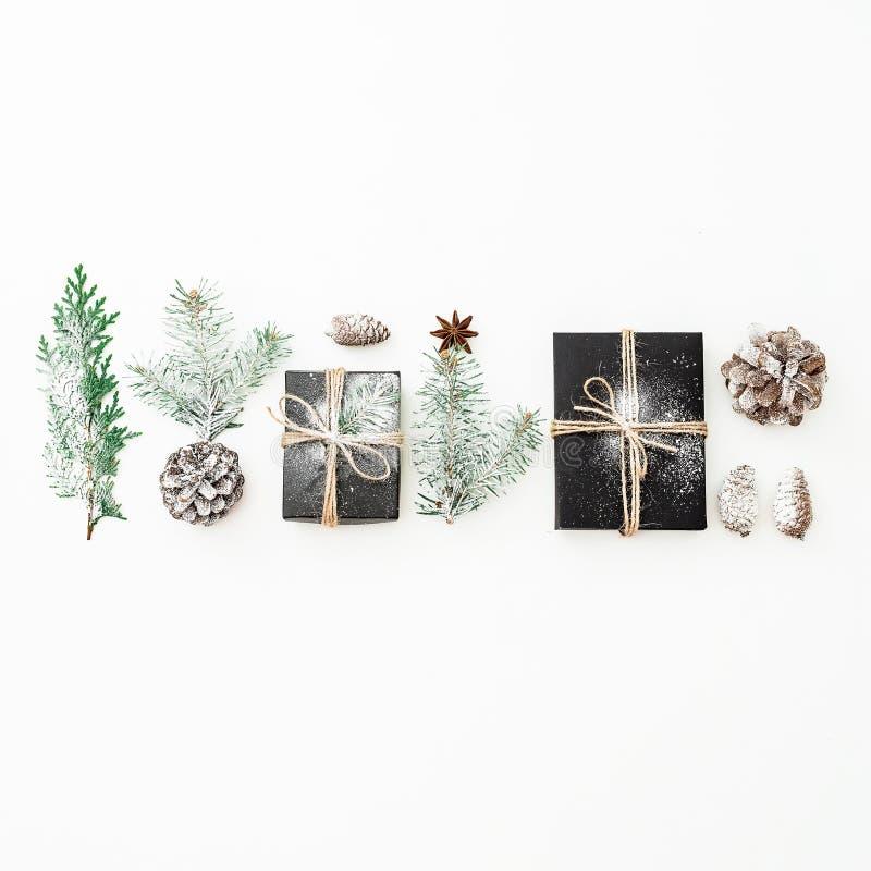 Состав рождества черной подарочной коробки с снегом, ветвями ели и конусами сосны на белой предпосылке Новый Год принципиальной с стоковое изображение