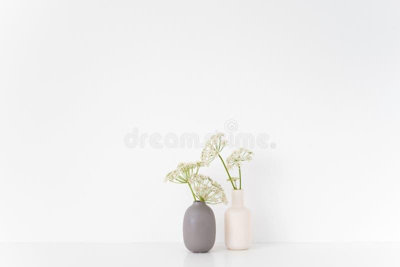 состав Серые и белые вазы с букетом Aegopodium на таблице на белой предпосылке стоковые изображения rf