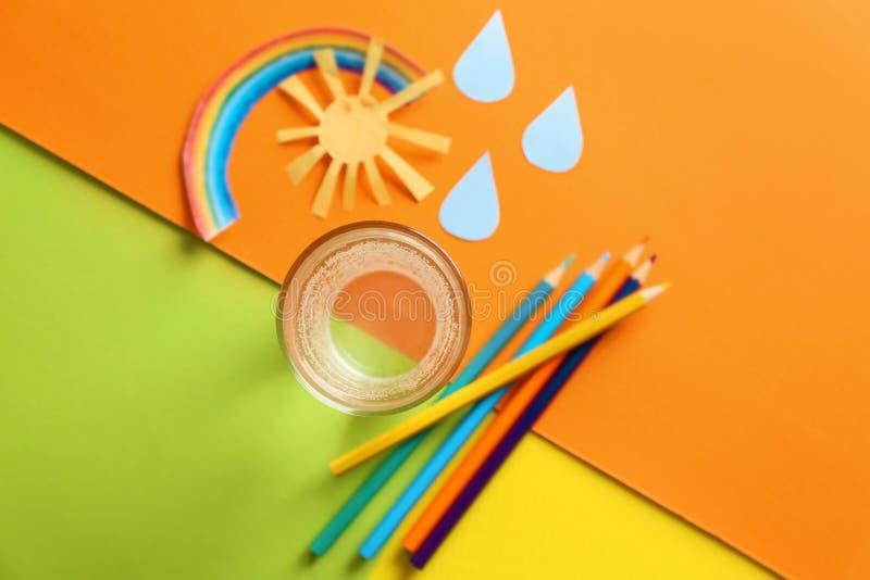Состав со стеклом свежей воды с карандашами на таблице цвета стоковая фотография rf