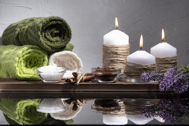 Состав спа 3 горящих свечи, цветок, зеленые полотенца и камешки стоковые изображения rf