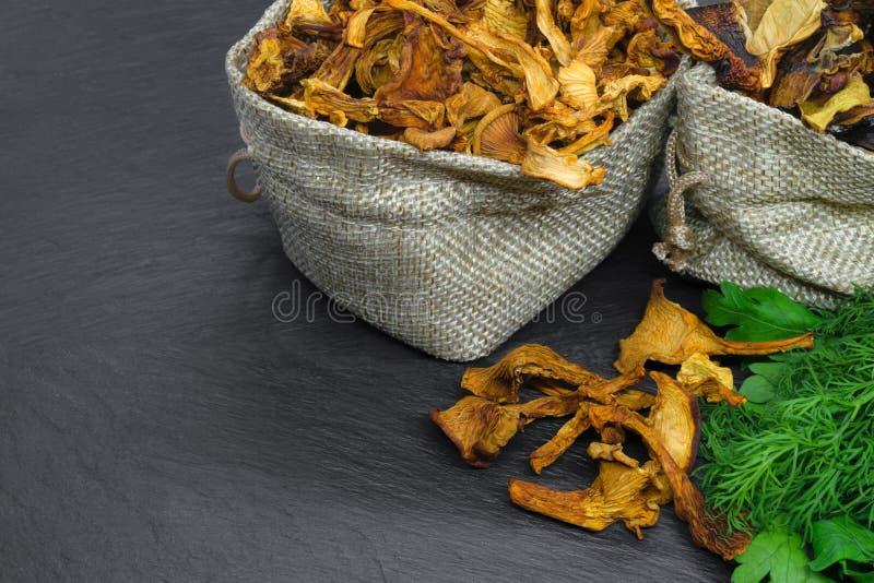 Состав сухих грибов подосиновика и лисичек помещенных в сумках холста с веником укропа и петрушки на черной каменной предпосылке стоковые фотографии rf