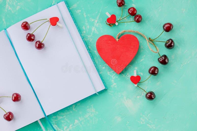 Состав с дневником и сладкими вишнями и ручкой, открытым блокнотом белой бумаги и оформлением с красной вишней, деревянным сердце стоковое изображение