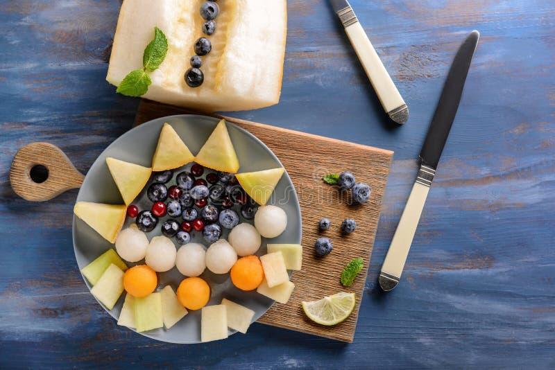 Состав с очень вкусными шариками и ягодами дыни на деревянном столе стоковая фотография