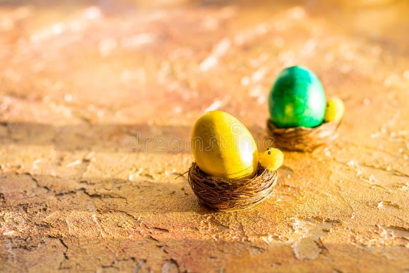 Состав с пасхальными яйцами в гнезде, на оранжевой предпосылке Пасхальное яйцо с космосом экземпляра для текста r E стоковая фотография rf