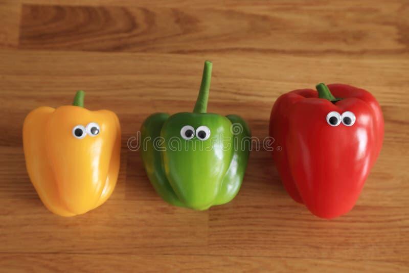 Состав с перцем цвета 3 - красными, зелеными, желтыми свежими сладким или болгарским перцем с глазами куклы на деревянной предпос стоковая фотография rf