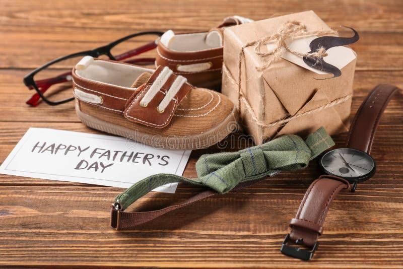 Состав с подарочной коробкой, небольшими ботинками и бабочкой на деревянной предпосылке Счастливый День отца стоковые фотографии rf