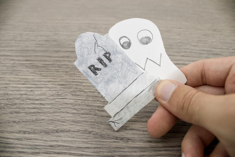 Состав хеллоуина, рука держит призрак и надгробную плиту o стоковое фото