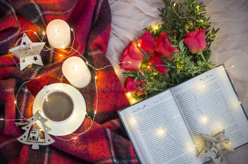 Состав: чай чашки кофе, красные розы с boxwood, книгой, свечами, гирлянды стоковое изображение rf