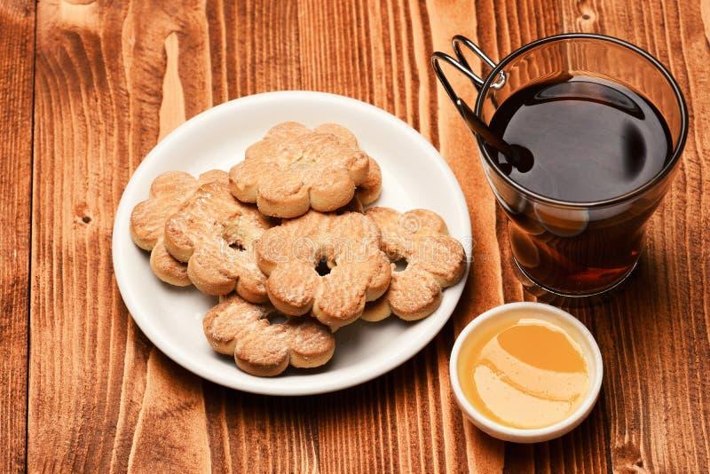 Состав чашки, меда и крошечного gateau на время чая стоковая фотография