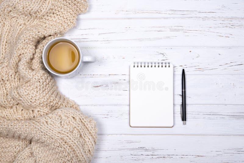 Состав чашки чаю, бежевой шотландки, тетради и ручки на белой деревянной предпосылке стоковая фотография