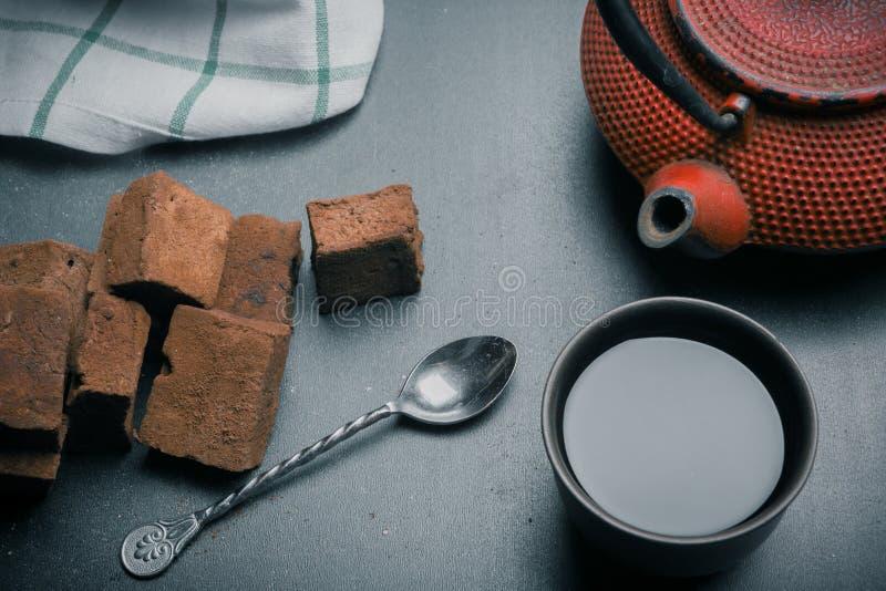 Состав чая с зефиром, чашкой чая и традиционным чайником на темной предпосылке стоковое изображение