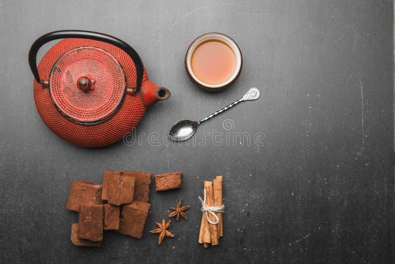 Состав чая с зефиром, чашкой чая и традиционным чайником на темной предпосылке стоковое фото
