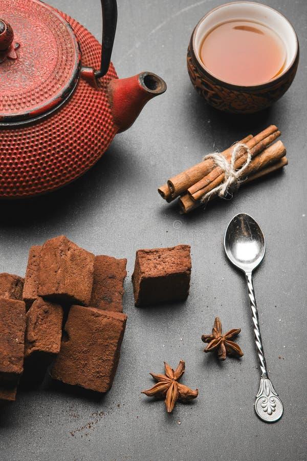 Состав чая с зефиром, чашкой чая и традиционным чайником на темной предпосылке стоковая фотография