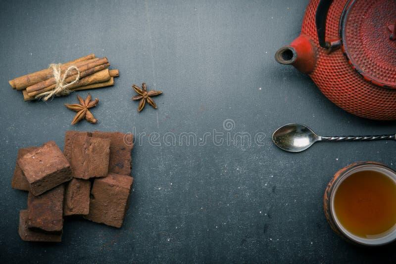 Состав чая с зефиром, чашкой чая и традиционным чайником на темной предпосылке стоковые фото