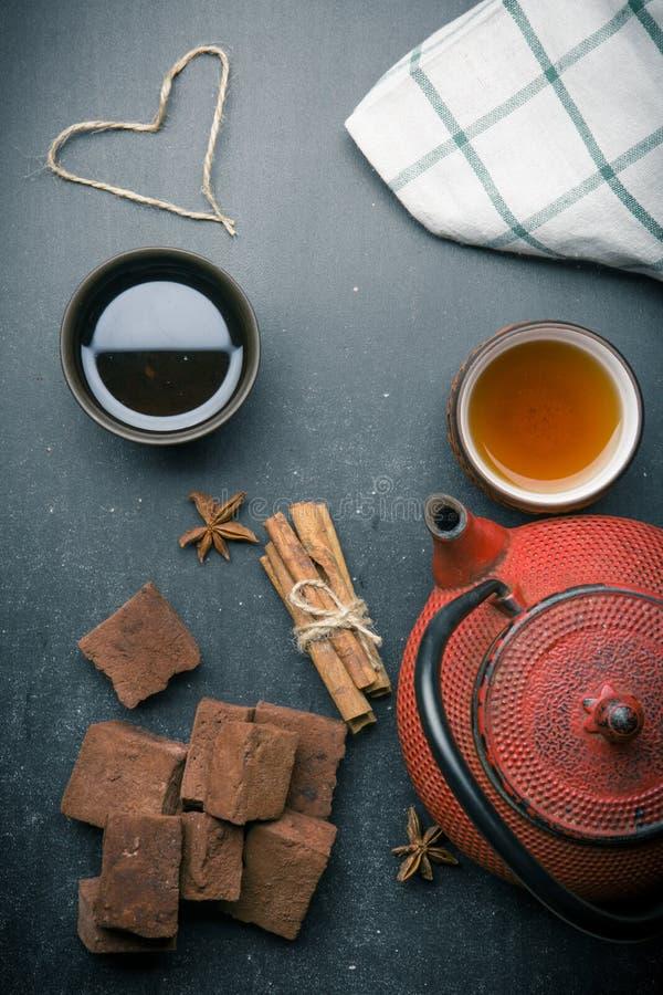 Состав чая с зефиром, чашкой чая и традиционным чайником на темной предпосылке стоковые изображения
