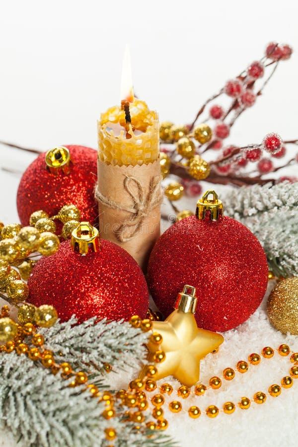 Состав Xmas с красными безделушками, гирляндой золота, свечой и лентой на белом снеге Предпосылка рождественской открытки стоковое изображение