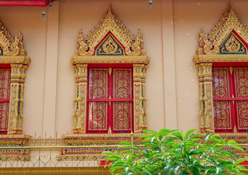 Состоятельное окно в золотых и красных цветах в тайском виске стоковая фотография rf