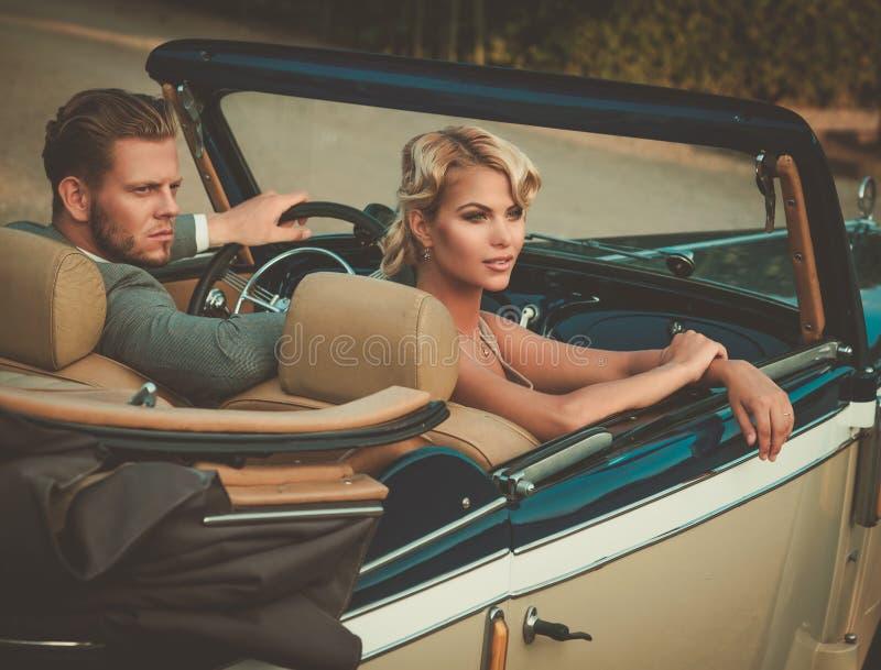 Состоятельные молодые пары в классическом автомобиле с откидным верхом стоковое фото rf