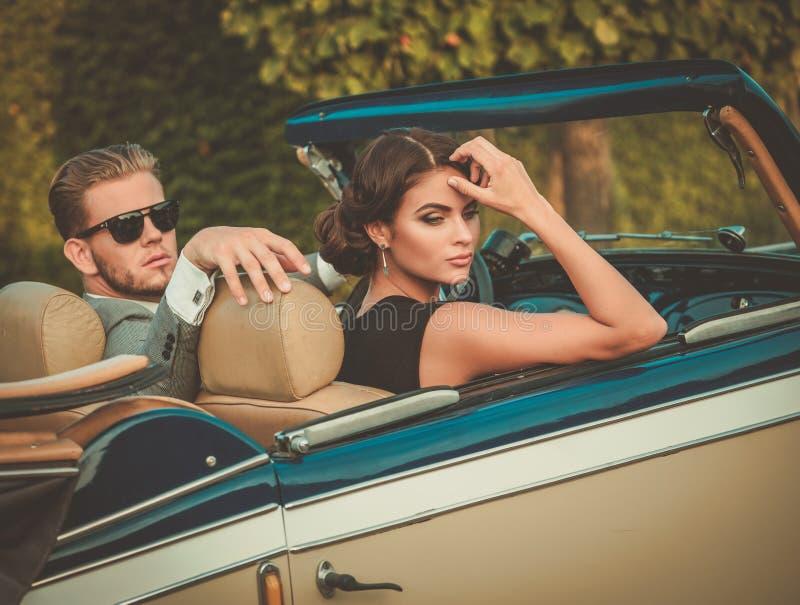 Состоятельные молодые пары в классическом автомобиле с откидным верхом стоковые фото
