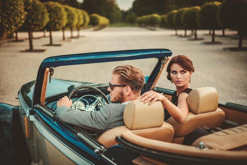 Состоятельные пары в классическом автомобиле с откидным верхом стоковая фотография
